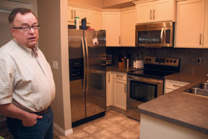 Shane Lacusta stands in the kitchen of the basement suite below his house. He put in brand new appliances so they wouldn't have to worry about maintenance right away, and so that tenants (perhaps one day his children) would have a nice kitchen. Photo by April Lamb