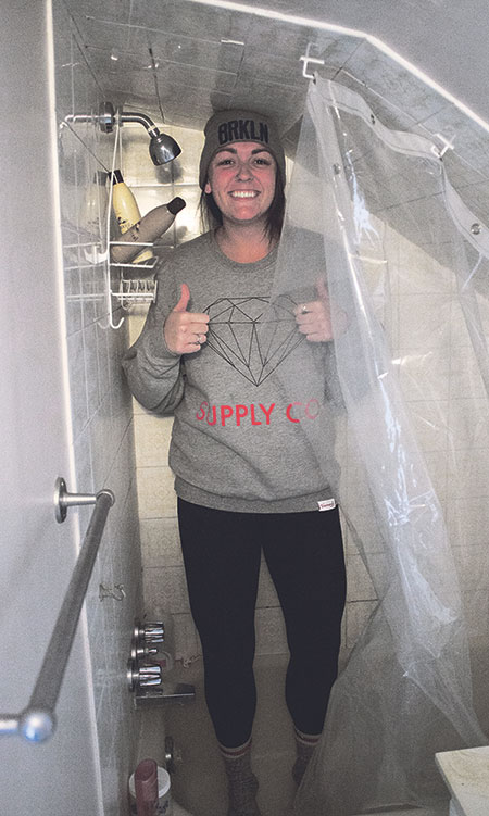 Fraser demonstrates the tiny size of the shower of her Mission secondary suite.